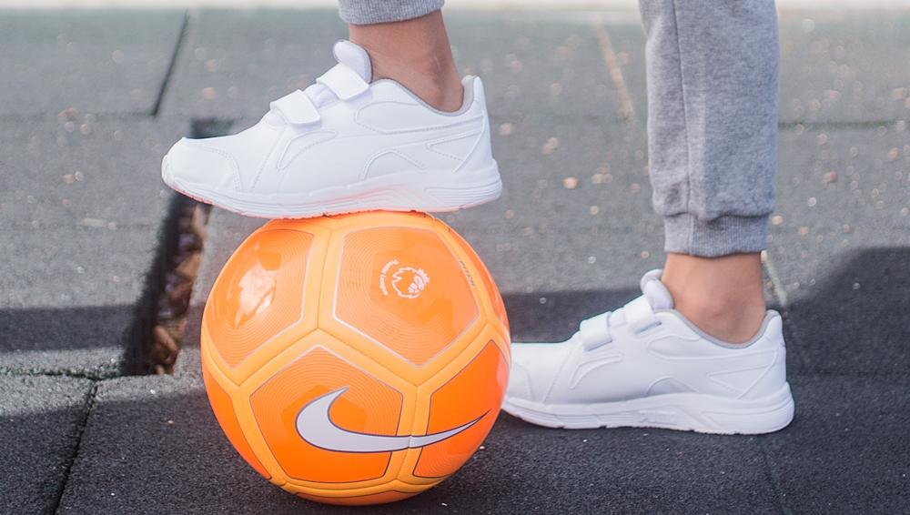 zapatillas blancas y balón de fútbol