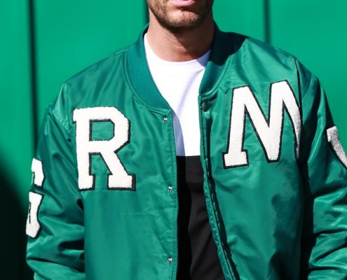 Chaqueta verde con letras grandes en blanco