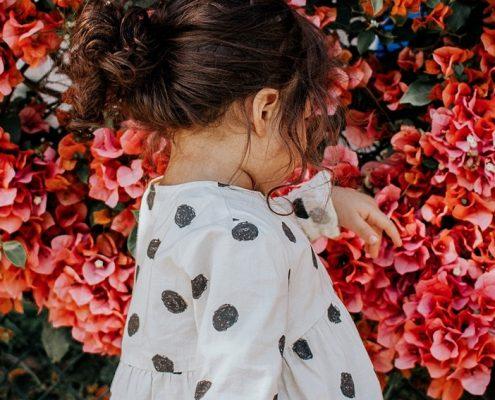 Portada niña junto a flores