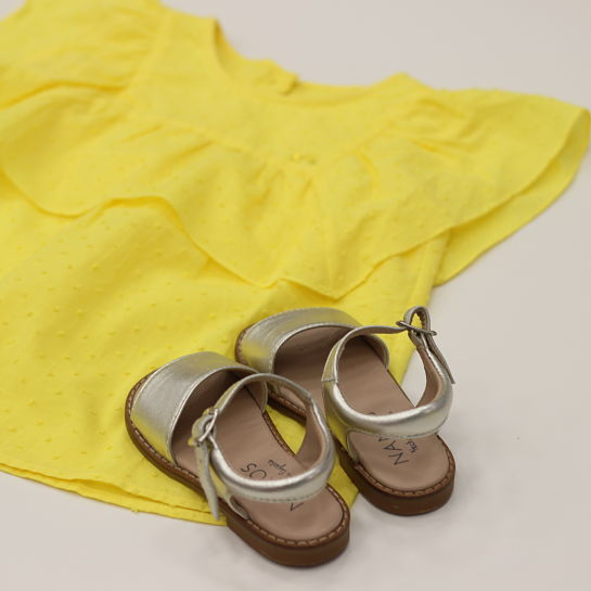 Nanos blusa amarilla sandalias beige